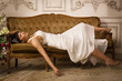 Bride in white dress lying on the sofa