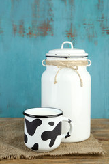 Retro can for milk and mug of milk on wooden table