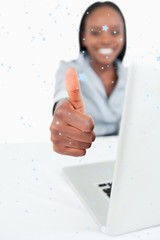 Businesswoman using a laptop with the thumb up