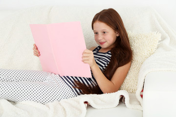Beautiful little girl reading book on sofa in room