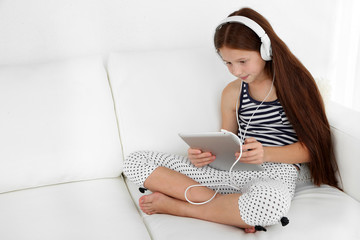 Beautiful little girl listening to music on sofa in room