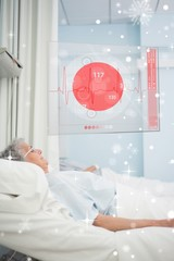 Patient lying in hospital bed with futuristic ecg data display