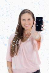Composite image of young woman showing a smartphone screen