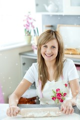 Portrait of a delighted woman preparing a cake in the kitchen