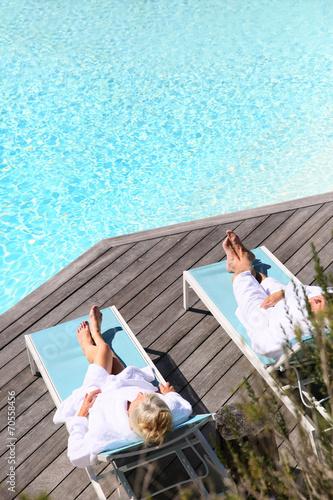 Leinwandbild Motiv Senior couple relaxing by swimming pool in spa hotel