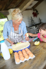 Grandmother cooking apple pie with little girl