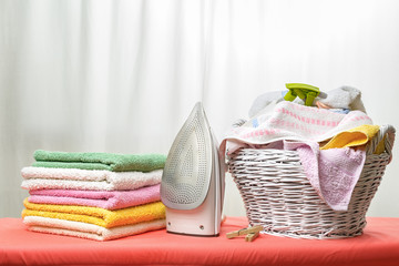 White iron and laundry in the white wicker basket on the ironing