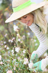 Smiling woman with hat gardening aromatic plants