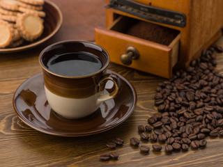 Kaffeetasse mit Kaffeemühle und Keksen