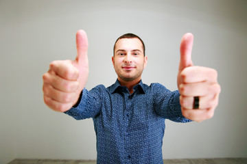 Portrait of a happy man with thumbs up over gray background