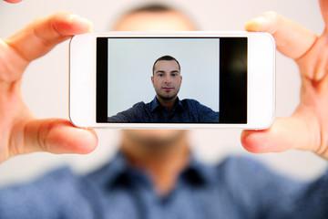 Handsome man taking selfie. Focus on smartphone