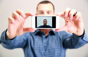 Happy man taking selfie. Focus on smartphone
