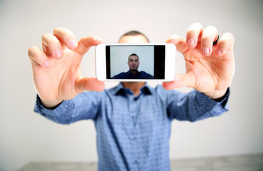Portrait of a man taking selfie. Focus on smartphone