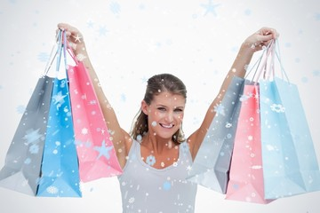 Composite image of woman holding shopping bags