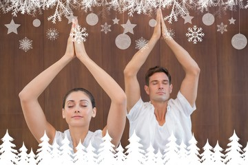 Peaceful couple in white doing yoga together with hands raised