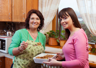 Mother and daughter talking, tasting food in kitchen