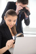 Businesswoman observing laptop with magnifying glass.