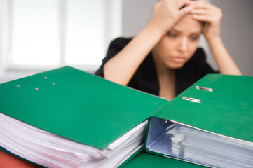 Business woman sitting at table covered with folders.