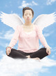 Young woman meditating with wings