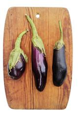 three eggplant on a wooden cutting board