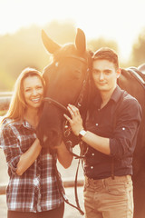 Portrait of a smiling couple with horse