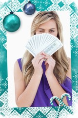 Blonde woman winking an eye while holding bank notes