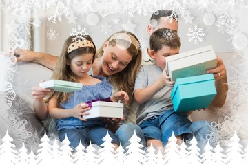 Composite image of family opening gifts on sofa