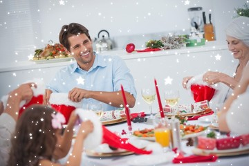 Composite image of cheerful family dining together