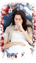 Composite image of sick woman drinking water lying on the sofa