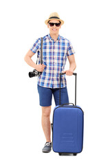 Young male tourist posing with his baggage