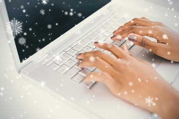 Close up on womans hands typing on her laptop