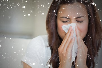 Composite image of brunette blowing nose into tissue