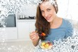 Smiling young woman eating fruit salad in kitchen