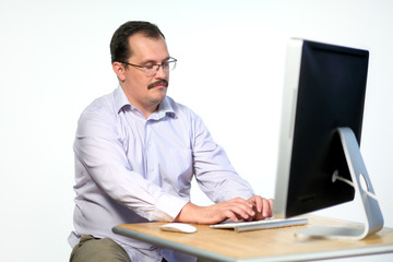Tired employee in glasses asleep while working on computer