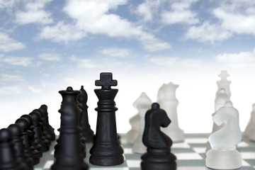 chess pieces isolated against cloudy sky