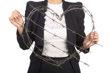 Girl  holding a heart of barbed wire fence