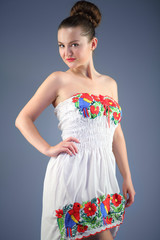 sexy young woman in a white dress with embroidery