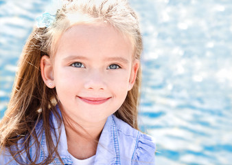 Outdoor portrait of cute little girl near the sea