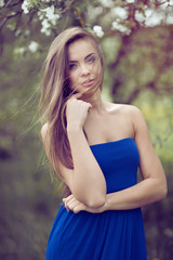 Beautiful young girl in blue dress posing in the park