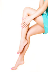Woman touching her beautiful legs. Isolated on white