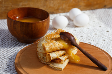 Russian pancakes with wooden spoons, honey