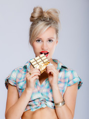 portrait of young woman sexy girl eating chocolate on blue