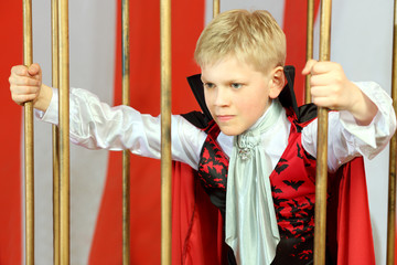 Boy in red cloak breaks free from golden cage