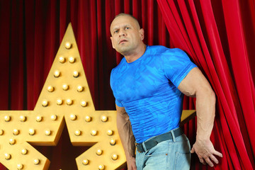 Strong man in blue t-shirt enters scene from behind scenes