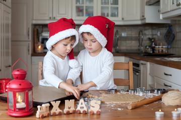 Two cute boys with santa hat, preparing cookies in the kitchen