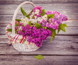White basket with a branch of lilac. Toning