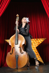 Portrait of a beautiful girl contrabass on stage at music hall