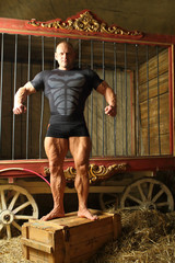 Strong man with big muscles around cell for wild animals