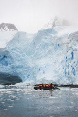 People in small inflatible zodiac rib boats passing icebergs and ice floes on the calm water around small islands of the Antarctic.