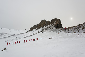 Travellers in bright orange waterproofs walking in a line across the snow on Deception island.